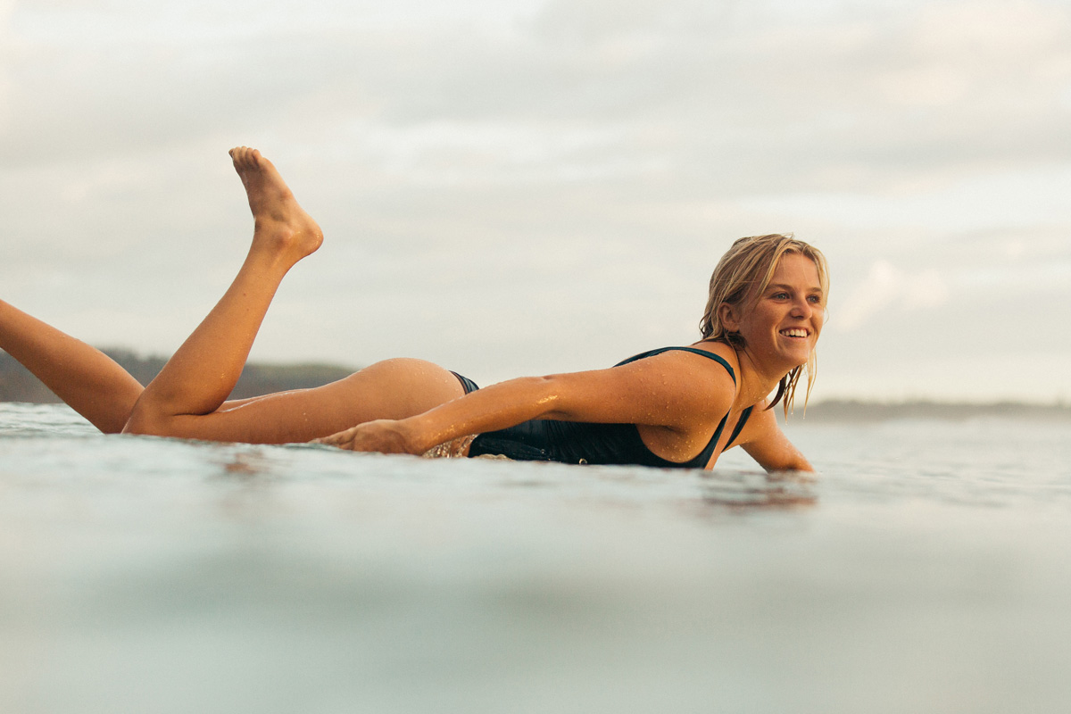 Woman paddling on surfboard at sunset wearing one piece surf swimsuit