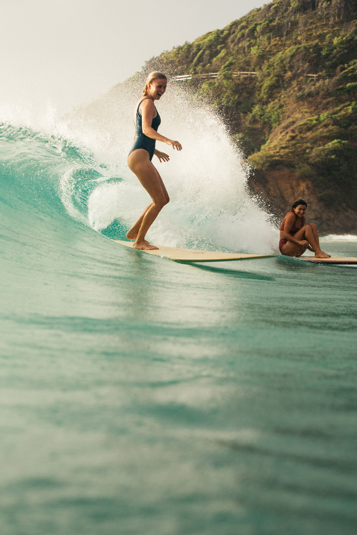 One girl surfing on a longboard wearing a one piece surf swimsuit.