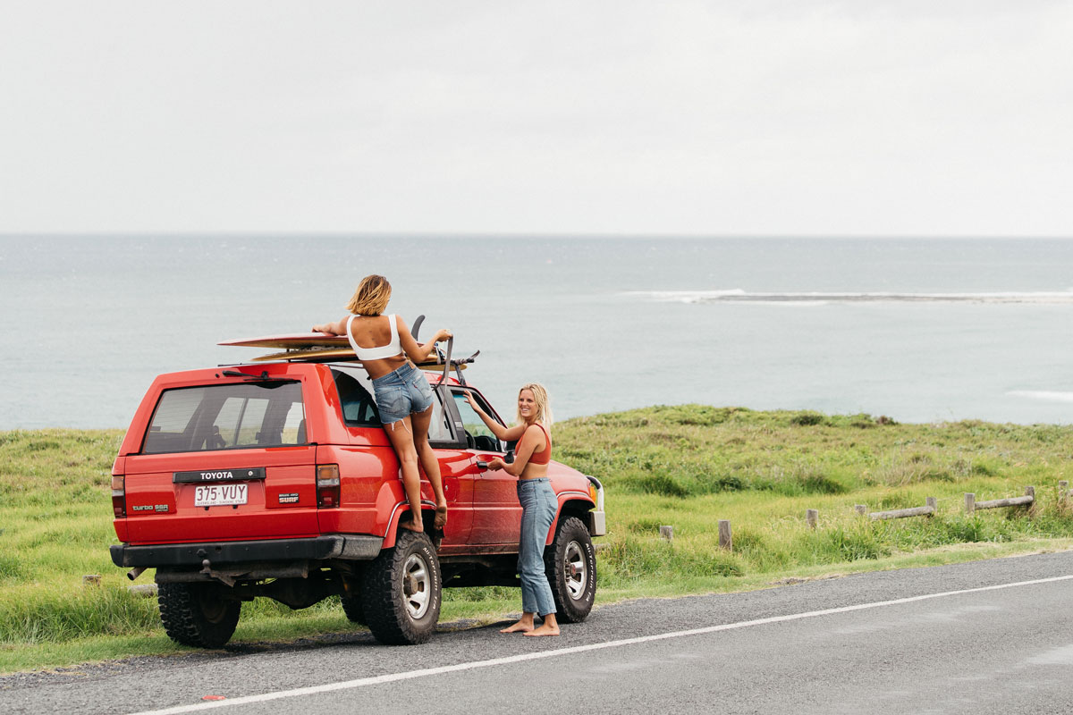 Two girls trying their longboards on top of the roof of a red toyota truck over looking the ocean