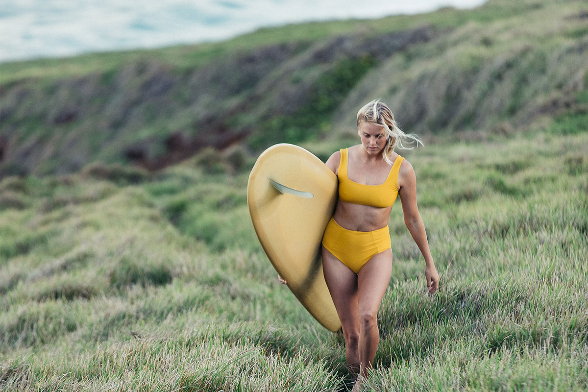 Woman walking in grass field in yellow surf bikini with surf board under her arm.