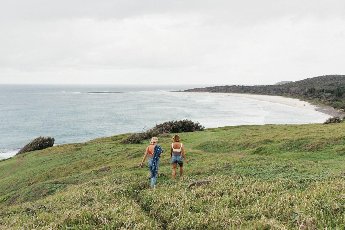 Two girls walking through grass field overlooking the ocean