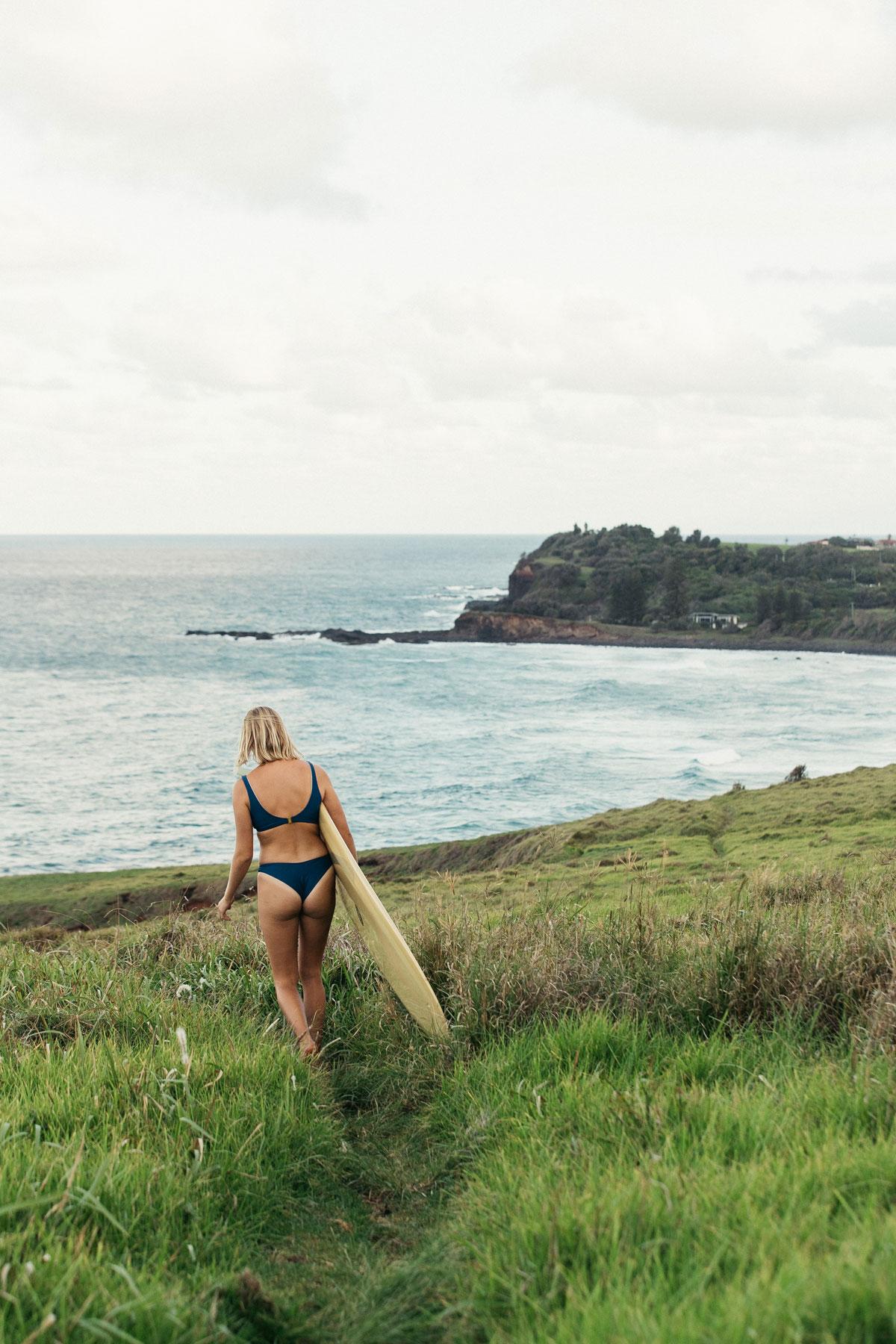 Woman walking in grass field towards the ocean wearing a blue surf bikini holding a longboard under her arm
