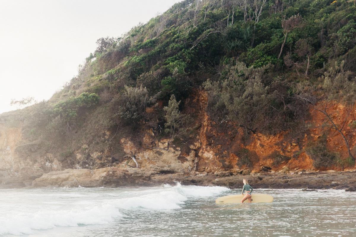 Woman walking into the ocean with surfboard wearing a rash guard and surf bikini bottoms