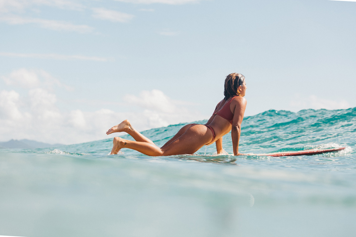 Woman laying on a surfboard looking over the wave wearing a surf bikini in burnt sienna