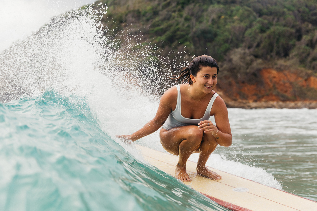 Woman smiling crouching down surfing on a longboard wearing a one piece surf swimsuit in ivory