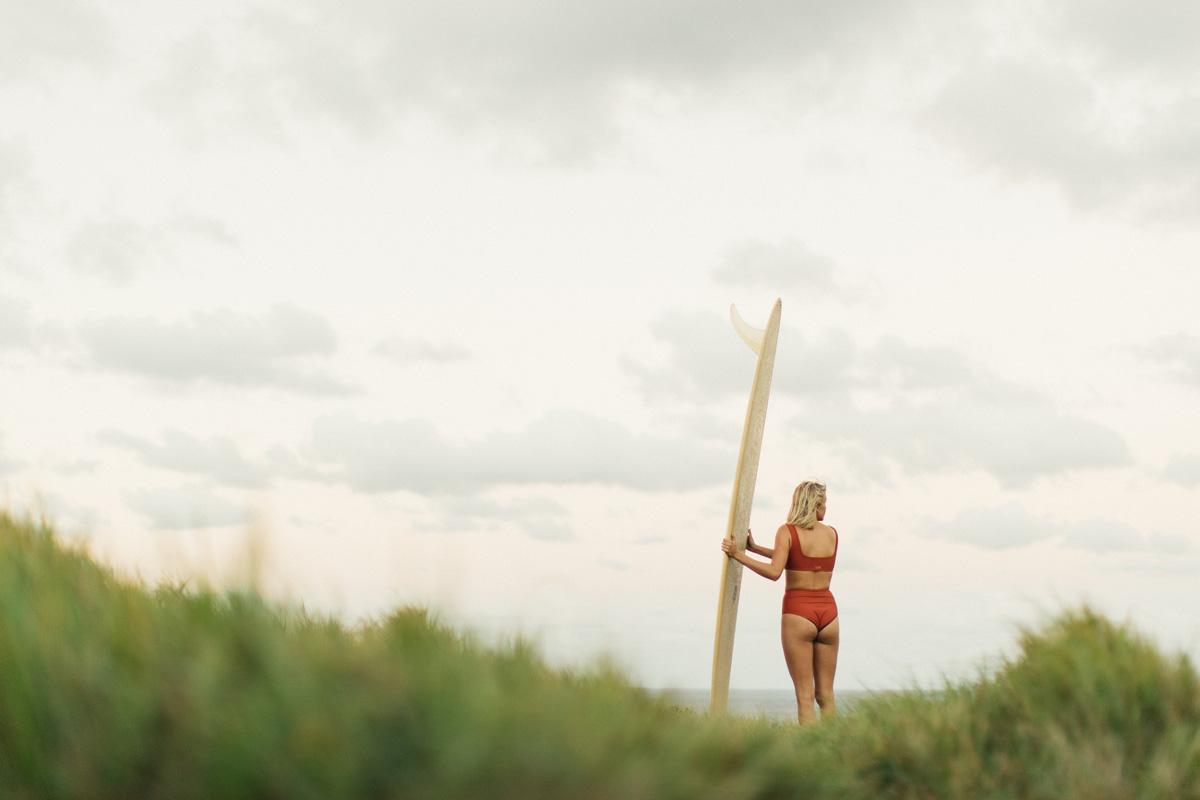 Woman standing in grass field looking at the ocean holding a longboard surfboard wearing a surf bikini top and bottom in burnt sienna